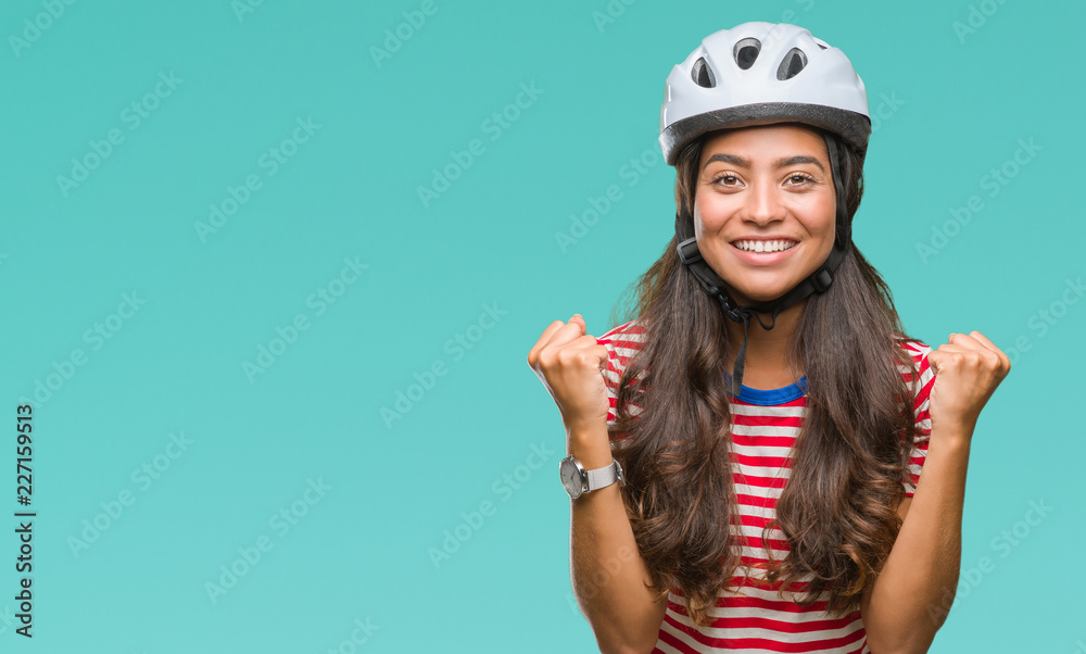 Fototapeta Young arab cyclist woman wearing safety helmet over isolated background celebrating surprised and amazed for success with arms raised and open eyes. Winner concept.