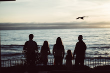 Family Feeding The Birds At Sunset Over Ocean