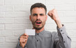 Young adult man over brick wall holding blank card annoyed and frustrated shouting with anger, crazy and yelling with raised hand, anger concept