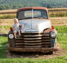 Little Boy On An Old Truck On A Farm