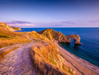 Leinwandbild Motiv Sunset over Durdle Door - the most famous landmark in Devon England