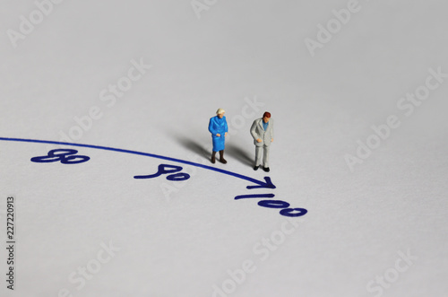 An old couple miniature standing before the number 100. Canvas Print