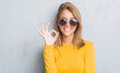 Beautiful young woman standing over grunge grey wall wearing retro sunglasses doing ok sign with fingers, excellent symbol