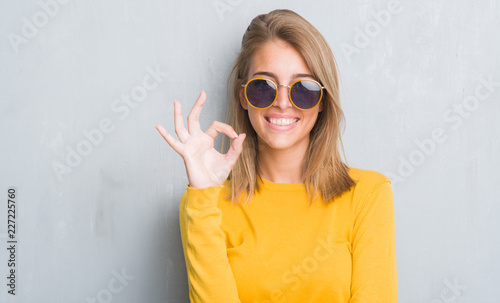 Carta da parati  Beautiful young woman standing over grunge grey wall wearing retro sunglasses do