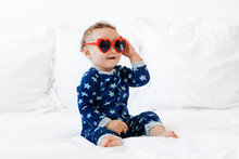 Cute Baby Sitting On White Bed Wearing Heart Sunglasses