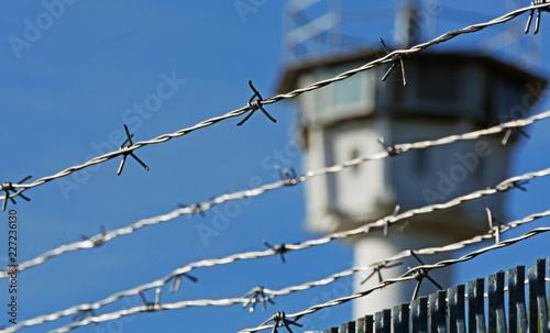 Fotomural  Stacheldraht mit Wachturm im Hintergrund