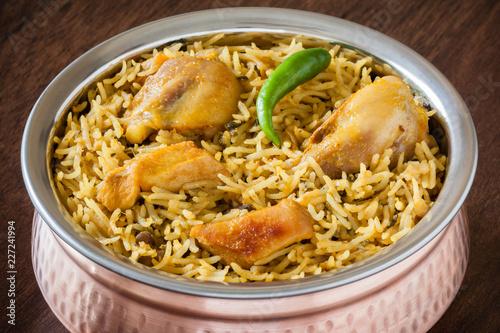 Chicken biryani closeup - Macro closeup view of delicious Indian chicken biryani served in authentic copper utensil. Natural light used.