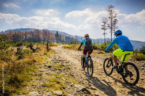 Photo sur Toile Cyclisme Mountain biking woman and man riding on bikes at sunset mountains forest landscape. Couple cycling MTB enduro flow trail track. Outdoor sport activity.