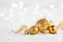 Christmas Golden Balls On Snow Over Abstract Winter Lights Background