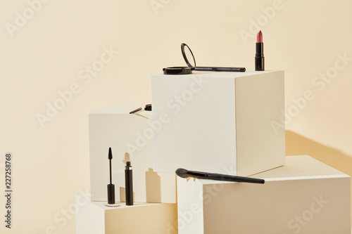 various makeup supplies lying on beige cubes