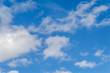 A deep blue sky with scattered clouds