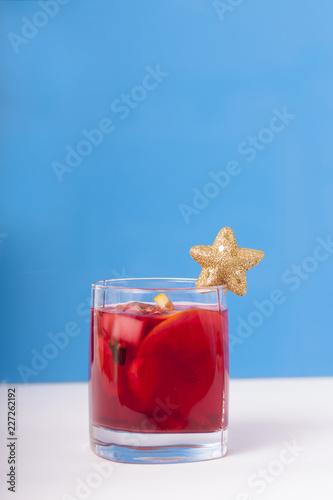 Staande foto Cocktail Стакан с коктейлем, украшенный золотой звездой на синем фоне