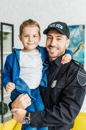 smiling young father in police uniform carrying his little son and looking at ca Fototapet