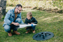 Father And Little Son Playing With Model Rocket On Grass