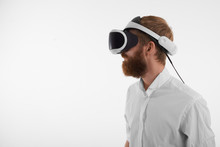 Visual Reality And Artificial Intelligence Concept. Profile Shot Of Bearded Red Haired Young Man Wearing Oculus Rift Headset Against Blank Studio Wall Background With Copy Space For Your Text