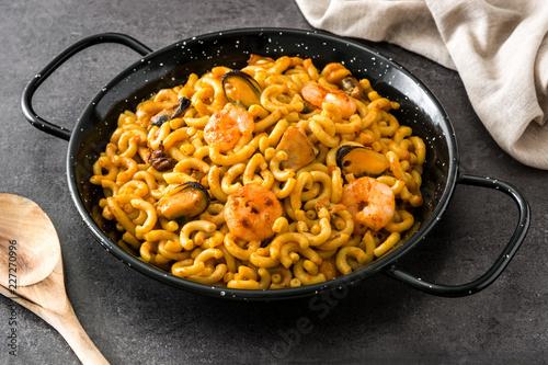 Traditional Spanish fideua. Noodle paella on black stone.