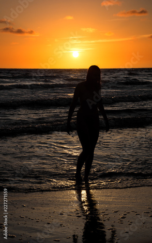 Poster Akt Silhouette of beautiful naked young woman posing in the sea