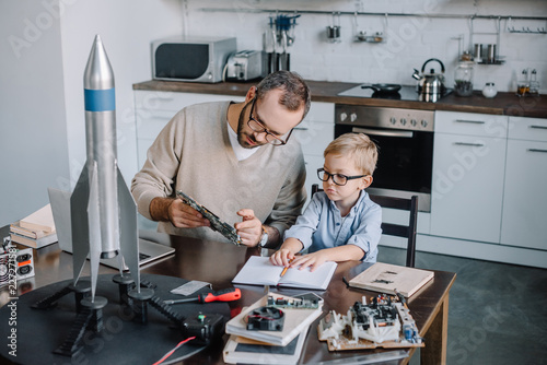 Photo  father and son repairing microcircuit at home
