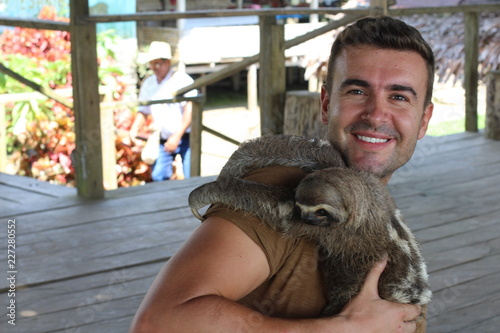 Sloth hugging a handsome man