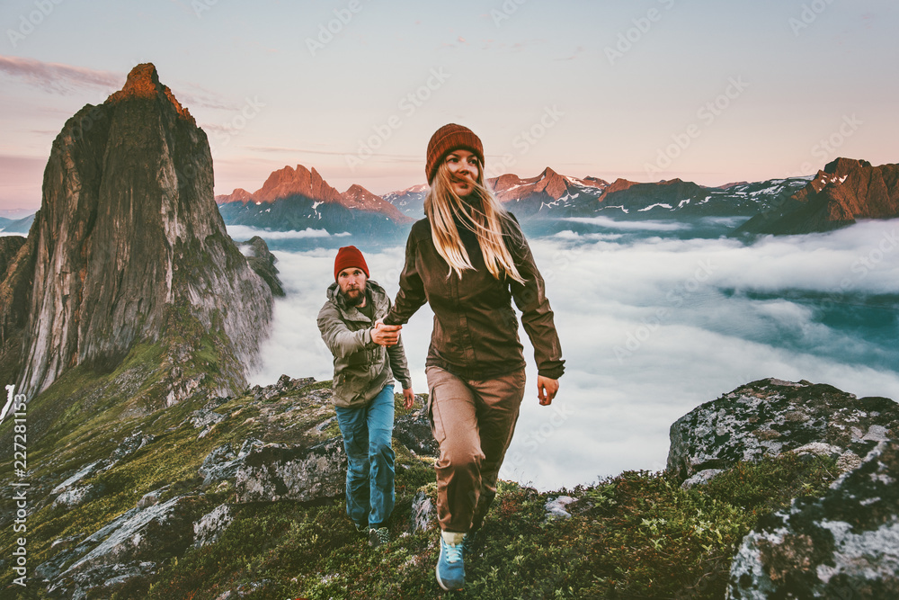 Fototapety, obrazy: Couple travelers holding hands hiking together in Norway travel healthy lifestyle concept active vacations outdoor Segla mountain sunset landscape