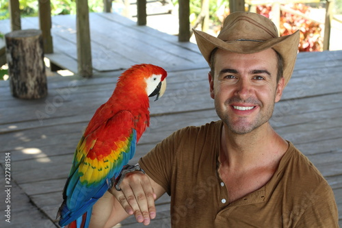 Handsome man interacting with a macaw