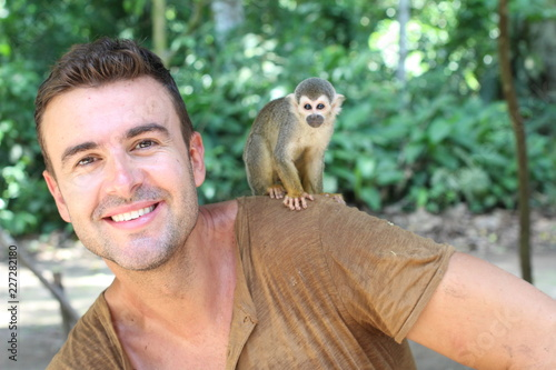Handsome man with titi monkey on his shoulder