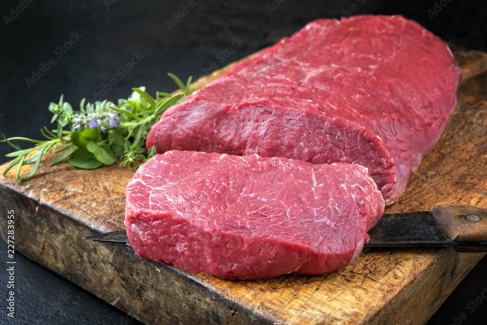 Fototapeta Raw roast beef with herbs offered as closeup on an old rustic wooden cutting board