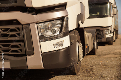 Photo Detail view of the front part of 18 wheeled trucks in the background of the second truck
