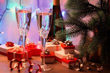 Two Glasses Of Champagne, A Christmas Tree And Many Small Gift Boxes. In The Background A Garland In Blur.