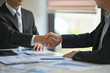 Cropped shot of two businessmen shaking hands in meeting room