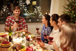 holidays and celebration concept - happy friends with glasses of wine having christmas dinner and speaking toast at home
