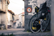 Travel Bike With Panniers Resting On A Wall In A Rural Village