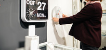 Wide Image Of Elegant French Woman Shopping For Clocks In Furniture Store - Diverse Types Of Wall Clocks Modern And Vintage