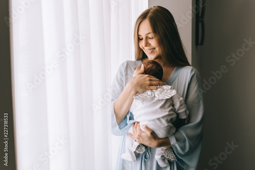 Obraz smiling attractive woman carrying little baby boy in front of curtains - fototapety do salonu
