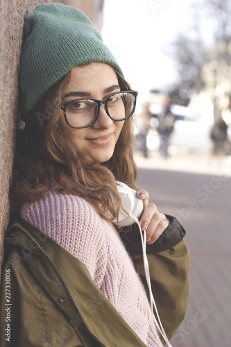 84816c518a8 Cute teenager girl in glasses and hat smiling stands on a city street.  Portrait of