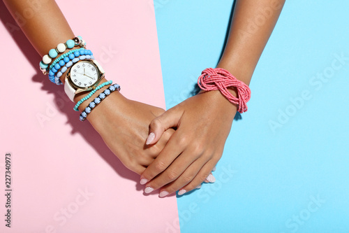 Female hands with bracelets on colorful background Canvas Print