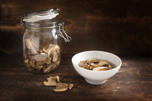 Dried Porcini Mushrooms In A Glass Jar And Soaked In Water As Preparation For Cooking On Dark Rustic Wood With Copy Space