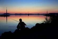 Silhouette Fishing Man At Coast Of Lake Balaton At Twilight