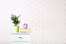 White Bedside Table With Books, Alarm Clock And Green Plant On Brick Wall Background