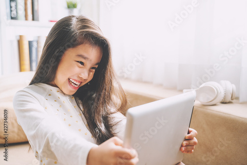 Young girl looking at digital tablet and smiling