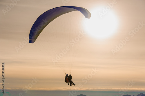 Foto op Canvas Luchtsport Couple of people flying on a parachute on the background of sky with big shining sky