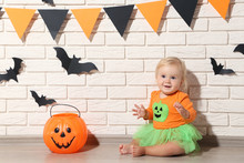 Baby Girl In Halloween Costume With Pumpkin Bucket