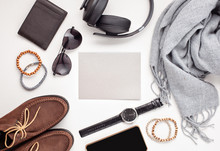 Flat Lay Of Men's Accessories With Shoes, Watch, Phone, Earphones, Sunglasses, Scarf Over The Orange Background