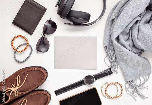 Fototapeta Flat lay of men's accessories with shoes, watch, phone, earphones, sunglasses, scarf over the orange background obraz