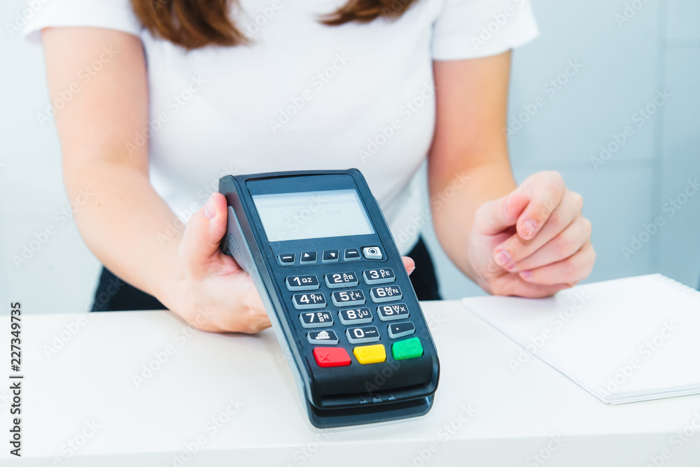 Fototapeta Seller holds payment terminal in hands. Contactless payment with nfc technology at shop, clinic, hotel. Mobile payment PayPass. Selective Focus on hands. Copy space.