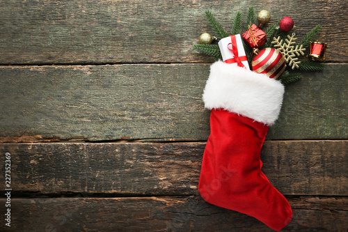 Fototapeta Red stocking with fir-tree branches and christmas decorations on wooden table