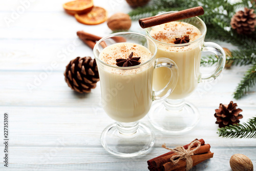 Fotobehang Cocktail Eggnog in glasses with cinamon and star anise on wooden table