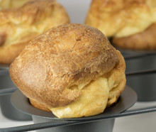 Homemade Popover, Which Is A Puffed, Airy, And Eggy Hollow Roll, Is Fresh From The Oven In A Dedicated Metal Pan With Two More Blurred Popovers In The Gray Background.