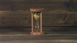 Sandglass clock on wooden table, setting time