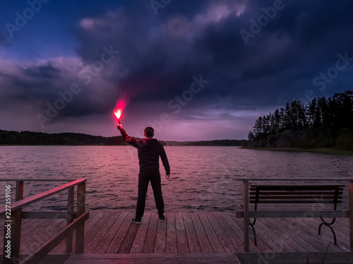 A man at the lake lit the signal bomb. SOS. Help signal. The man at the pier is holding signal block. The man on the quay. Torch with fire.